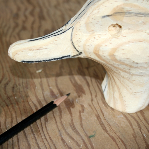 48. Mark the curved line between the bill and cheek. Note that the hinge (at the bottom of the bill) is aft of the process at the top of the bill. Carve this first with the tip of the knife the shave very carefully with the belly of the knife.