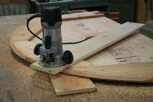 Radii are cut with the router fastened to a board that pivots on a single screw.